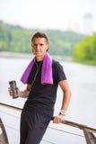 Junger Sportmann mit Tuch und Flasche Wasser Stockfotos