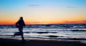 Junger Sportswoman, der auf den Strand läuft Lizenzfreie Stockfotografie