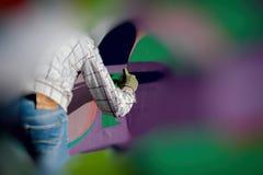 Junger städtischer Maler, der helle Graffiti auf der Wand zeichnet Abstrakte kreative Zeichnung Moderne ikonenhafte städtische Ku Stockbild