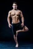 Junger starker Athlet macht Yoga auf schwarzem Hintergrund Lizenzfreie Stockfotografie