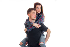 Junger starker Kerl hält auf seiner Rückseite ein schönes Mädchen und blickt in Richtung der Nahaufnahme Stockfoto