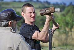 Junger starker Mann, der Landeigentum einzäunt Lizenzfreies Stockfoto