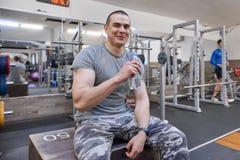 Junger starker muskulöser Mann in Trinkwasser der Turnhalle von der Flasche lizenzfreie stockfotografie