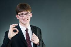 Junger stattlicher Geschäftsmann, der okayzeichen zeigt Stockfoto