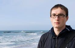 Junger stattlicher Mann in den Gläsern gegen einen Hintergrund Stockbild