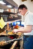 Junger stattlicher Mann, der Abendessen vorbereitet stockfoto