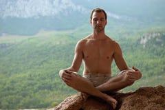Junger stattlicher Mann, der auf Felsen meditiert lizenzfreie stockbilder