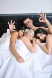 Junger stattlicher Mann, der im Bett mit drei Mädchen liegt Lizenzfreies Stockbild