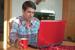 Junger stattlicher Mann, der mit Kaffee und Laptop sitzt Stockbild