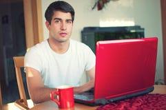 Junger stattlicher Mann, der mit Kaffee und Laptop sitzt lizenzfreie stockfotografie