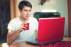 Junger stattlicher Mann, der mit Kaffee und Laptop sitzt stockfoto