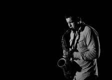 Junger stattlicher Mann, der Musik auf Saxophon spielt Lizenzfreies Stockfoto