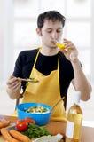 Junger stattlicher Mann, der Salat auf Küche kocht Lizenzfreie Stockfotografie