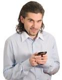 Junger stattlicher Mann lächelt und hält Handy an Stockfotografie