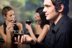 Junger stattlicher Mann mit Glas Rotwein und zwei Frauen stockfotografie
