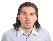 Junger stattlicher Mann setzt heraus seine Zunge Stockfotos