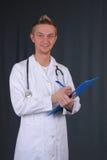 Junger stattlicher Manndoktor auf grauem Hintergrund Stockbilder
