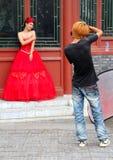 Junger stilvoller Fotograf, der ein Foto eines schönen Mädchens im roten Kleid für Heiratsportfolio macht Stockfotos