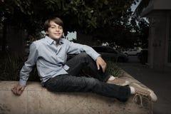 Junger stilvoller Junge, der auf einer Leiste sitzt Lizenzfreies Stockbild