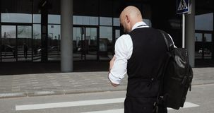 Junger stilvoller kahler Geschäftsmann, der zum Geschäftszentrum, Flughafen, Büro geht Konzept: ein neues Geschäft, reisend die W stock video
