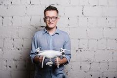 Junger stilvoller Mann in den Gläsern, die das quadcopter Brummen DJI Phantom 4 auf einer grauen Backsteinmauer halten Lizenzfreie Stockfotografie