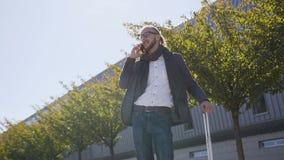 Junger stilvoller Mann, der auf seiner Telefonstellung mit Koffer nahe modernem Bürogebäude spricht draußen Konzept des Geschäfts stock footage