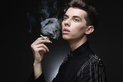Junger stilvoller Mann, der eine Zigarette raucht Lizenzfreies Stockfoto