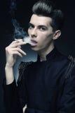 Junger stilvoller Mann, der eine Zigarette raucht Stockfotos