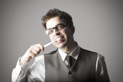 Junger stilvoller Mann mit den Brillen, die Zähne putzen Lizenzfreie Stockbilder