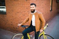 Junger stilvoller Mann mit einem Bart, der auf Fahrrad auf einem Ziegelsteinhintergrund sitzt Stockbilder