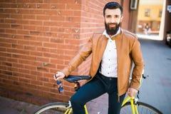 Junger stilvoller Mann mit einem Bart, der auf Fahrrad auf einem Ziegelsteinhintergrund sitzt Lizenzfreie Stockfotos