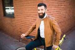 Junger stilvoller Mann mit einem Bart, der auf Fahrrad auf einem Ziegelsteinhintergrund sitzt Lizenzfreies Stockfoto
