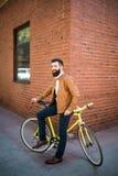 Junger stilvoller Mann mit einem Bart, der auf Fahrrad auf einem Ziegelsteinhintergrund sitzt Stockbild