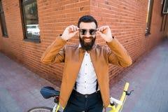 Junger stilvoller Mann mit einem Bart in der Sonnenbrille, die auf Fahrrad auf einem Ziegelsteinhintergrund sitzt Lizenzfreies Stockbild