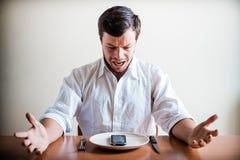 Junger stilvoller Mann mit weißem Hemd und Telefon auf dem Teller Lizenzfreie Stockbilder