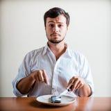 Junger stilvoller Mann mit weißem Hemd und Telefon auf dem Teller Stockfotografie
