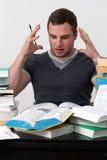 Junger Student überwältigt mit dem Studieren Lizenzfreie Stockbilder