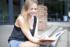 Junger Student außerhalb des Lesebuches und -c$lächelns Stockfotos