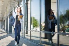 Junger Student der Frau IT, mit Büchern und Rucksack Gehen zu konferieren und Unterhaltung am Telefon stockfotografie