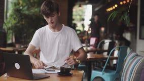 Junger Student, der Hausarbeit im Café, Freiberufler unter Verwendung des Bleistifts tut, um auf Papier, moderner Arbeitsplatz zu stock footage