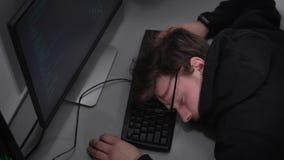 Junger Student der Lehrkörpers auf Informationstechnologie schläft auf Tastatur im frint des Computermonitors nach stark stock video footage