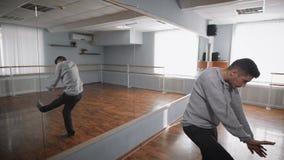 Junger Student der Tanzschule stehend nahe dem Spiegel und Wissen des modernen Tanzes im Ballsaal zeigend jung stock footage