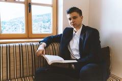 Junger Student, der vor hellem Fenster lernt Lizenzfreie Stockfotos
