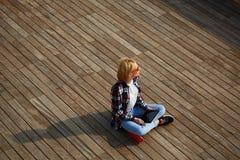 Junger Student des blonden Haares, der auf dem hölzernen Pier weg schaut, Aufflackernsonne sitzt stockfotos