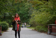 Junger Student geht in den Herbst Park mit einem Handy in der Hand Stockbilder