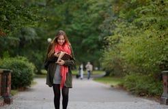 Junger Student geht in den Herbst Park mit einem Handy in der Hand Lizenzfreie Stockfotos