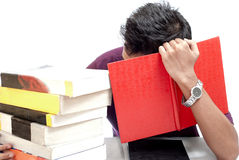 Junger Student Hiding His Face mit Buch Stockfotos