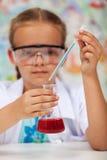 Junger Student im Chemieunterricht, der ein Experiment tut Lizenzfreie Stockbilder