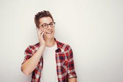 Junger Student im zufälligen roten Hemd sprechend auf Smartphone Lizenzfreie Stockfotos