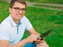 Junger Student mit Tablette draußen Stockfotografie